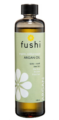Clear glass bottle with black cap. Label shows Fushi Organic argan oil.
