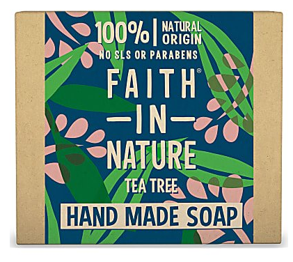 A natural brown rectangle card box with blue background illustrated with green leaves and pink flower blossoms, text on box shows faith in nature tea tree hand made soap.