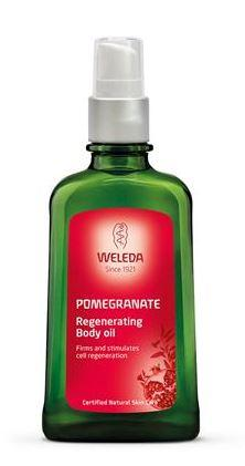 A green bottle with white atomiser cap. Red label shows weleda pomegranate regenerating body oil.