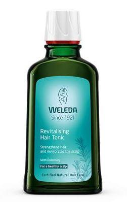 A green glass bottle with white cap. Blue label shows weleda revitalising hair tonic.