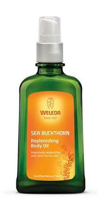 A green bottle with white atomiser cap. Orange label shows Weleda Sea Buckthorn Replenishing Body Oil.