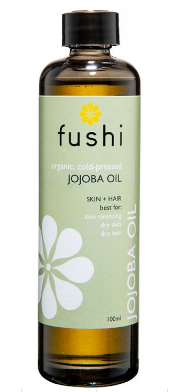 A brown glass bottle with black cap. Label shows Fushi organic jojoba oil.