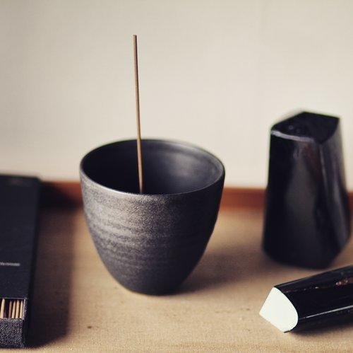 An wood table top image showing a black curved incense burner pot with incense stick, surrounded by black rectangular boxes.