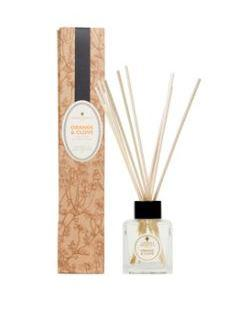 natural brown decorated box and clear glass bottle with ratten reeds labelled amphora orange and clove reed diffuser