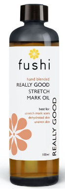 A brown glass bottle with black cap. Natural label has white flower image. Label shows Fushi really good stretch mark oil.