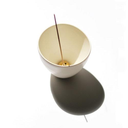 White porcelain curved pot shown with brass incense holder inside with incense stick inserted.