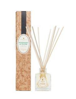 natural brown decorated box and clear glass bottle with ratten reeds labelled amphora rosemary and thyme reed diffuser