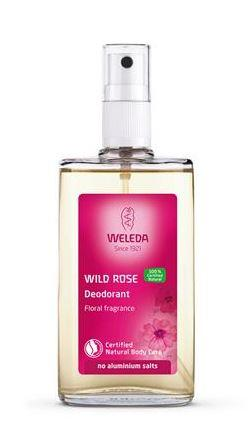 A clear glass bottle with pink label and atomiser spray top. Label shows weleda wild rose deodorant.