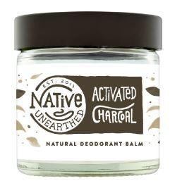 A clear glass jar with black lid containing a white balm. Black text on jar shows Native Unearthed activated charcoal deodorant balm.