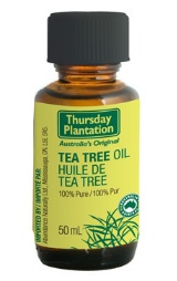 A brown glass bottle with black cap, green label shows Thursday Plantation tea tree oil.