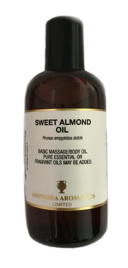 Brown plastic bottle with black cap. White label with black text shows sweet almond oil basic massage body oil.