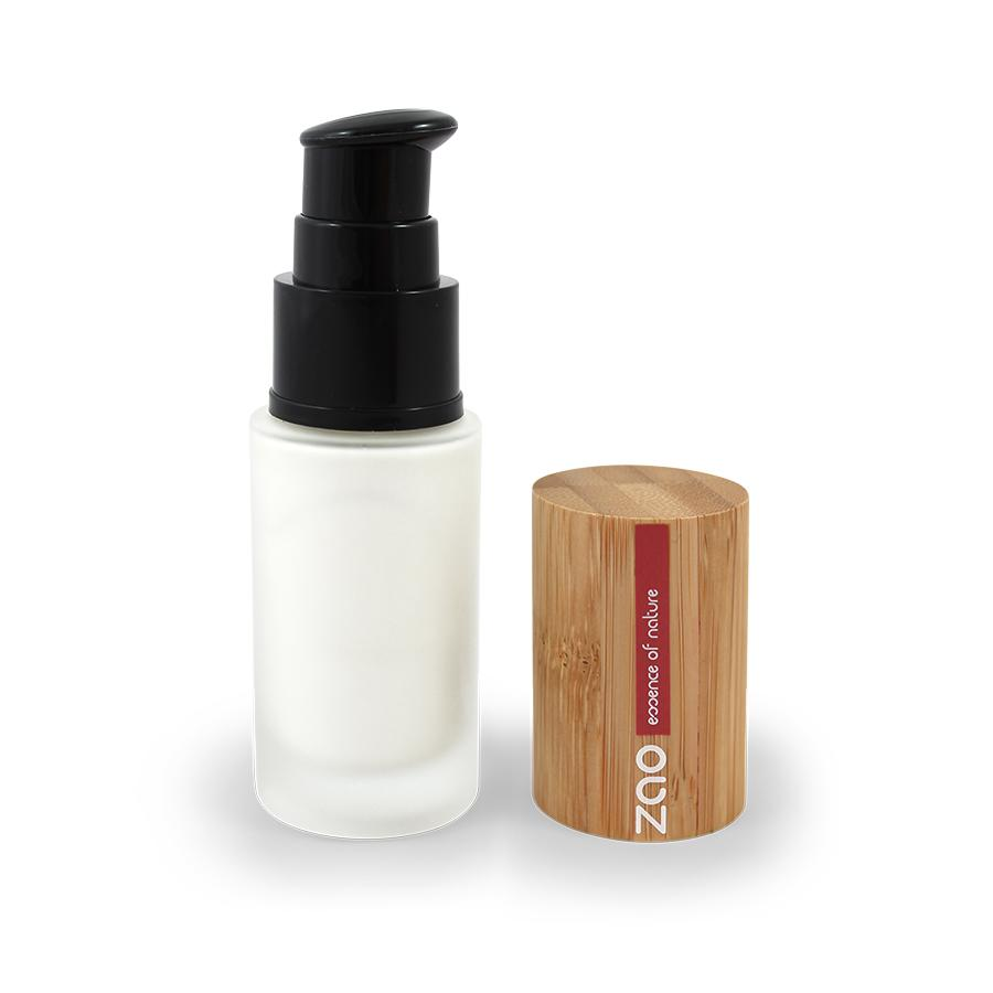 open clear glass bottle of white base make up primer, black pump dispenser, bamboo lid next to bottle, label shows Zao