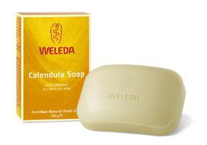 A rectangle smooth bar of off white soap, imprinted with Weleda, next to yellow box packaging. Labelling shows Weleda Calendula Soap.
