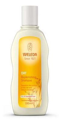 A white plastic bottle with white cap and orange label. Label shows weleda oat replenishing shampoo.