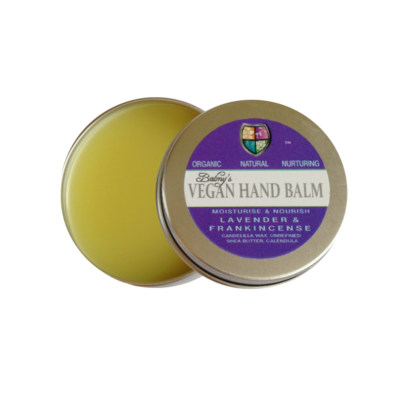 An open silver aluminium tin containing pale yellow solid balm, lid has dark purple and white label showing balmys vegan hand balm lavender and frankincense.