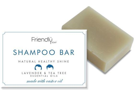 A natural cream rectangle shampoo bar, next to card box packaging of white and blue. Label shows friendly soap shampoo bar lavender and tea tree.