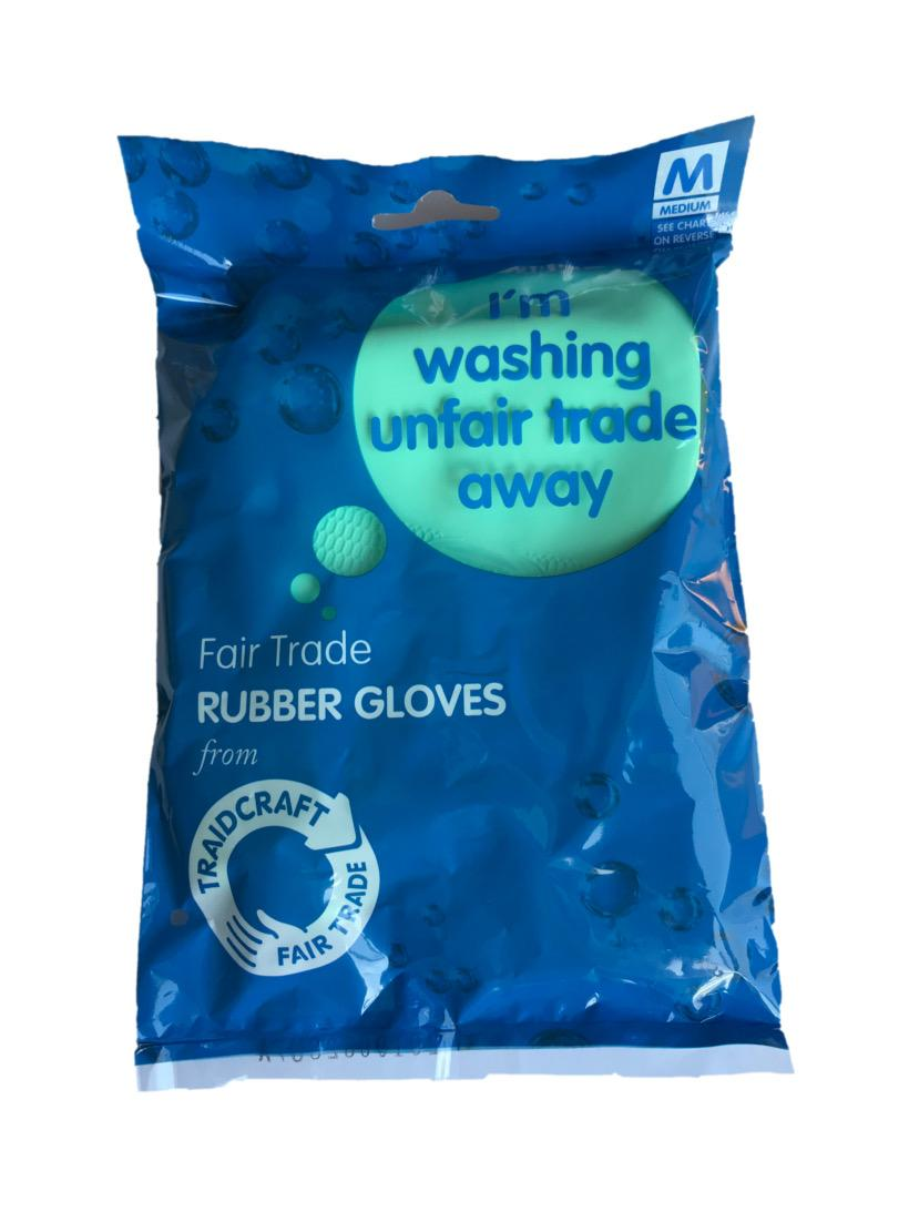 Blue plastic packaging with clear window showing green rubber gloves. Labeling shows fair trade rubber gloves