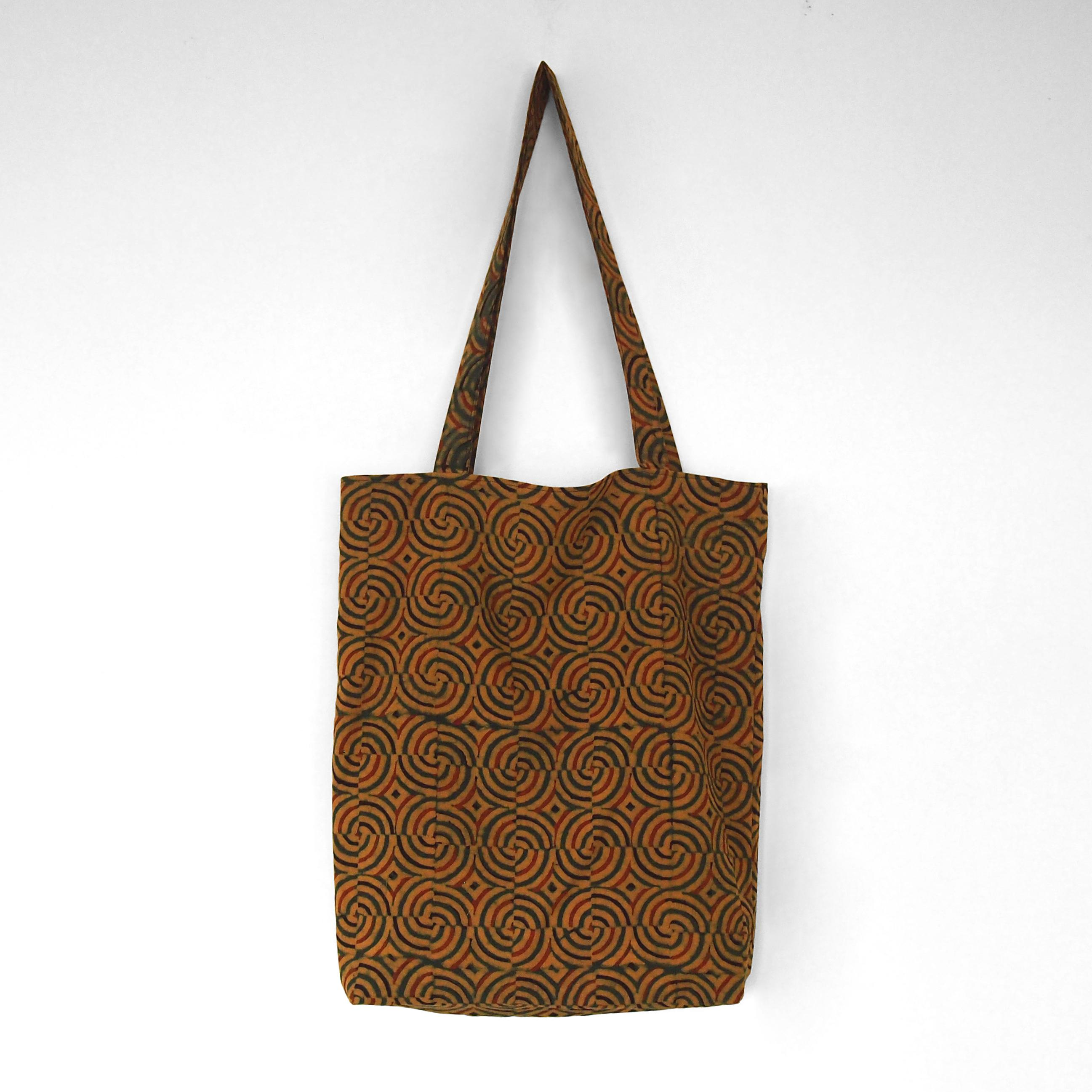 block printed cotton tote bag, yellow, green red black spiral design, natural dye, lined with black cotton, closed