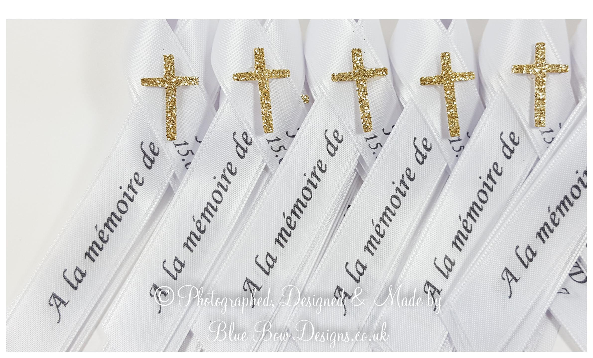 White memorial ribbon with gold cross and text