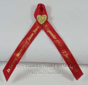 Red and gold memorial ribbon with gold heart and text