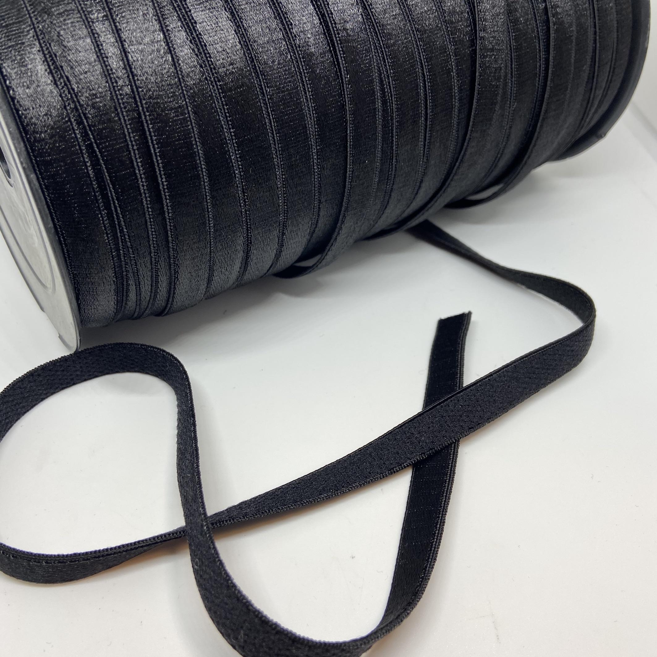 A full roll of a black shiny bra strap, with a soft back