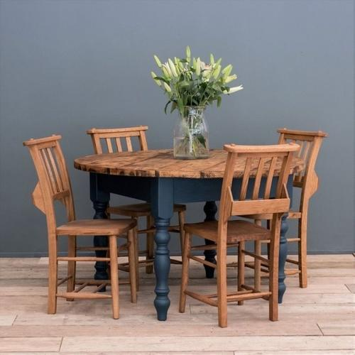 Rustic round farmhouse dining table and four chairs, the table and chairs are plain wood, the dining table legs are navy blue, on the table is a glass vase of white lilies.