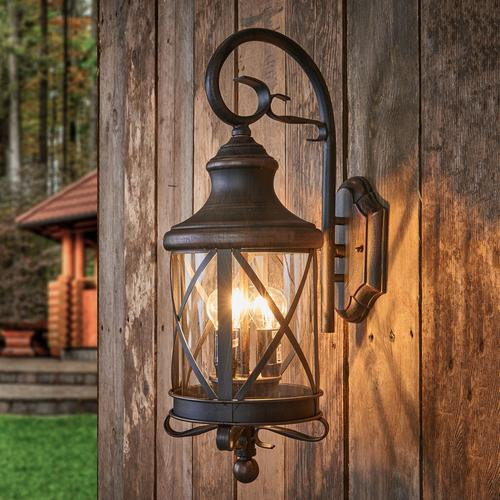 A single rustic wrought iron outdoor wall light in bronze, mounted on a old wooden shed wall, the wall light has two bulbs which produce a beautiful ambience.