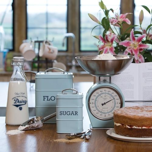 A country kitchen with vintage blue baking equipment on the worktop including, kitchen scales, flour and suger canisters, to the left is a glass bottle of milk and to the right a freashly baked victoria sponge.