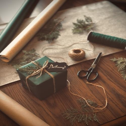 A single gift wrapped in dark green wrapping paper with a thin gold bow on a dark wood table, the black name tag simply says 'bethany' the gift has rolls of green and gold wrapping paper and scissors around it.