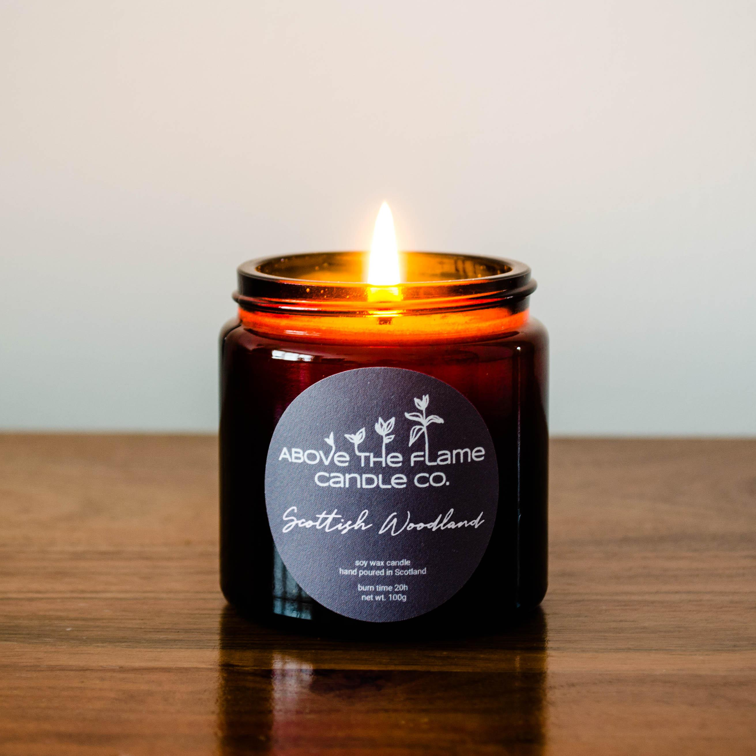 A lit scottish woodland amber soy wax candle jar handmade by above the flame candle Co on a wooden table