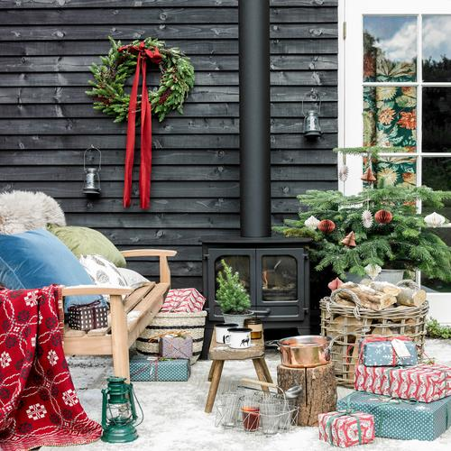 A rustic christmas out door setting with wood burner, log basket and wooden bench, all made cosy with cushions, blankets, presents and lanterns, oh and not forgetting mugs hot chocolate.