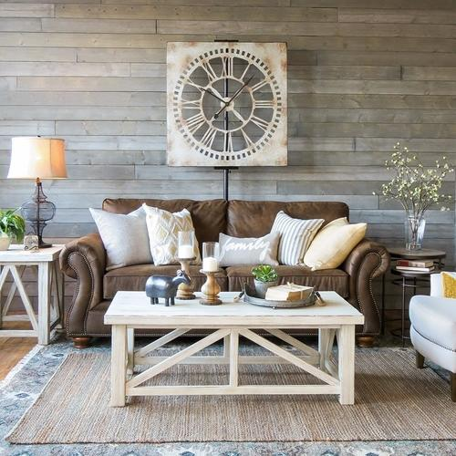 Farmhouse style living room, dark brown leather sofa with light coloured cushions, a large square rustic cream metal wall clock, rustic white tables, rugs, lamps, candles and other beautiful home accessories.