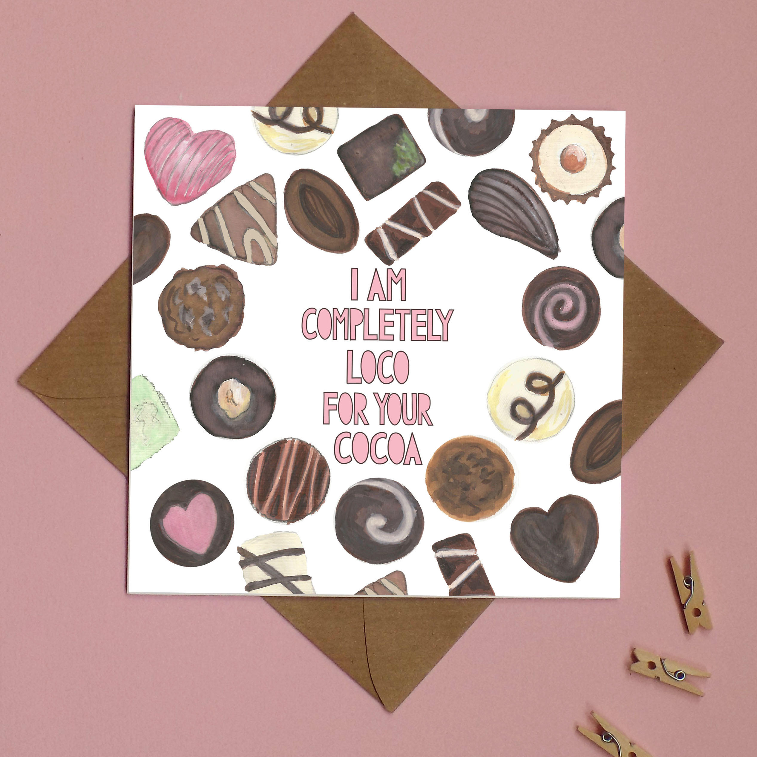 A square card with illustrations of chocolates and pink typographic text saying 'I am completely loco for your cocoa'