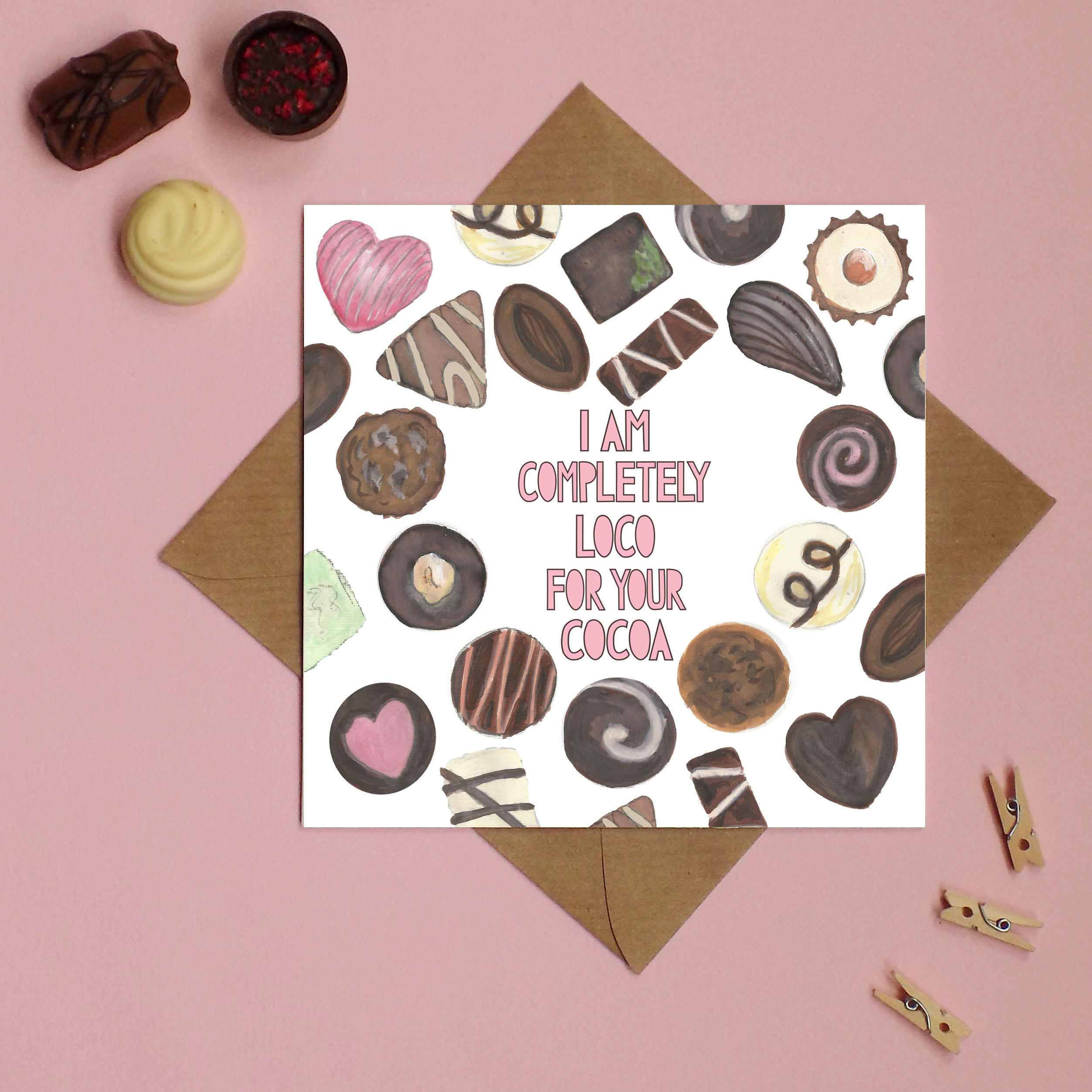 A side view of a greetings card with watercolour illustrations of chocolates on it and pink typographic text which says 'i am completely loco for your cocoa'