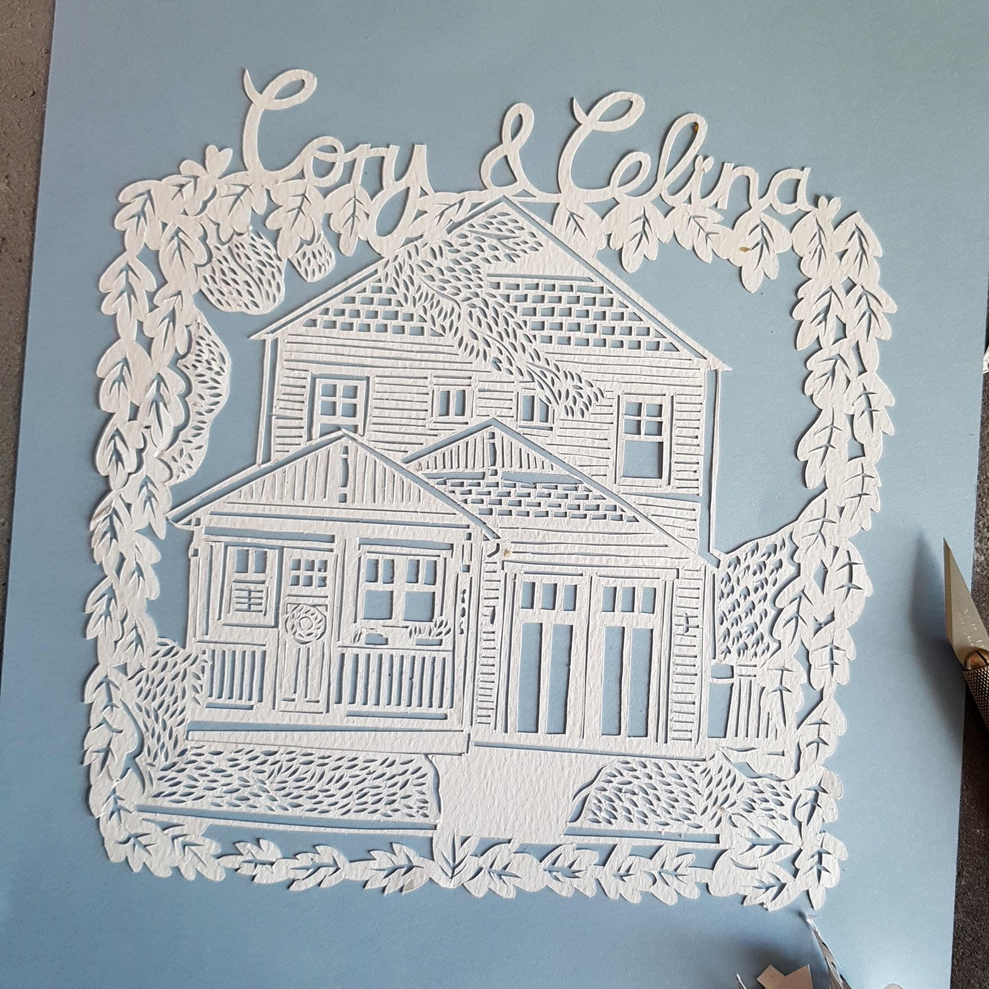 A hand drawn, hand cut paper cut of a house, personalised for a customer.