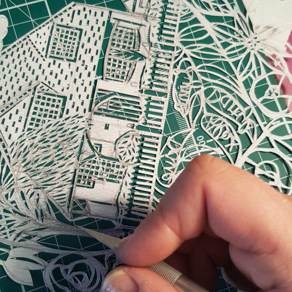 A second close up of a paper cut house portrait in action