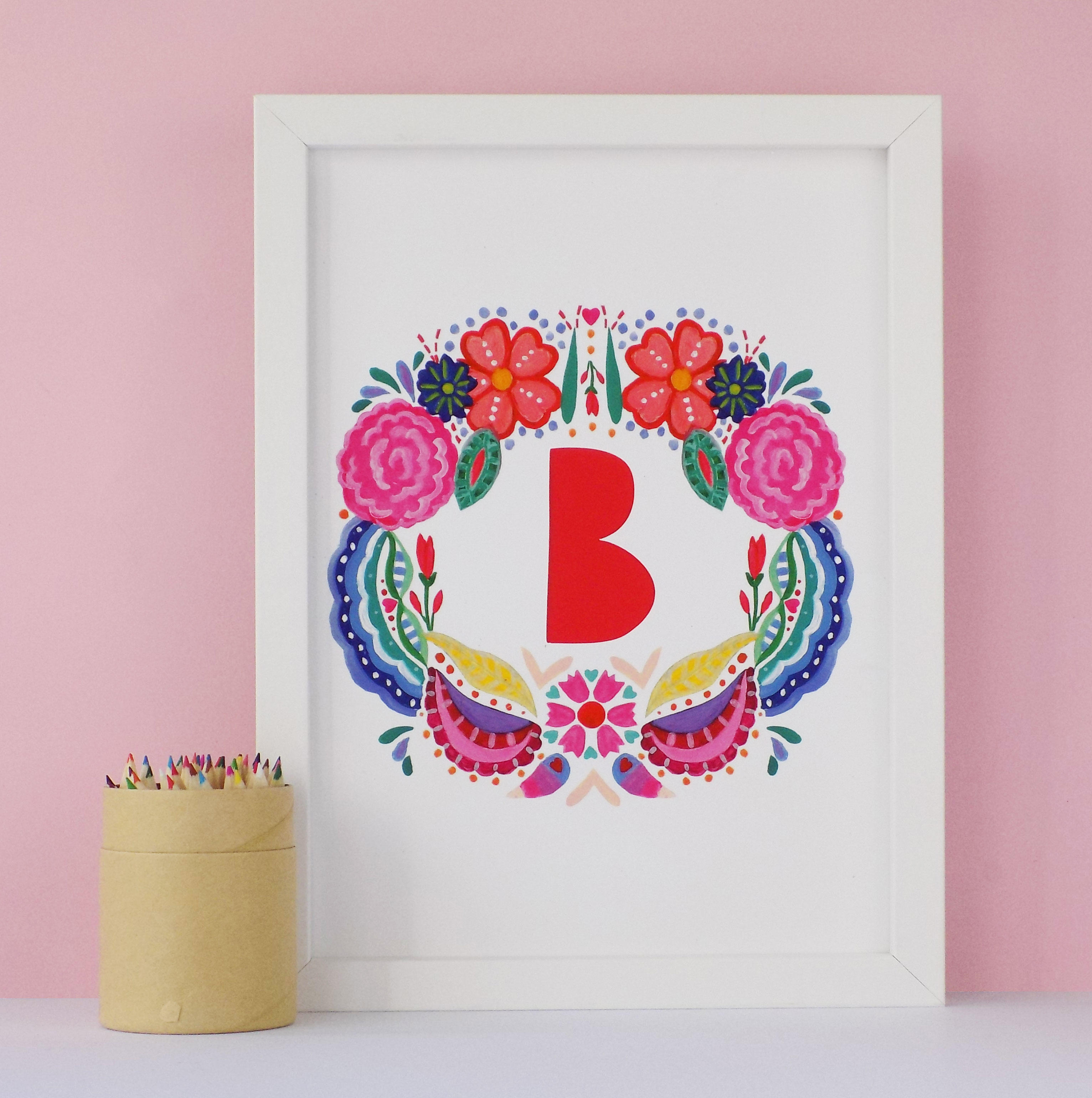 A bright watercolour floral print with a bold paper cut style typographic initial.