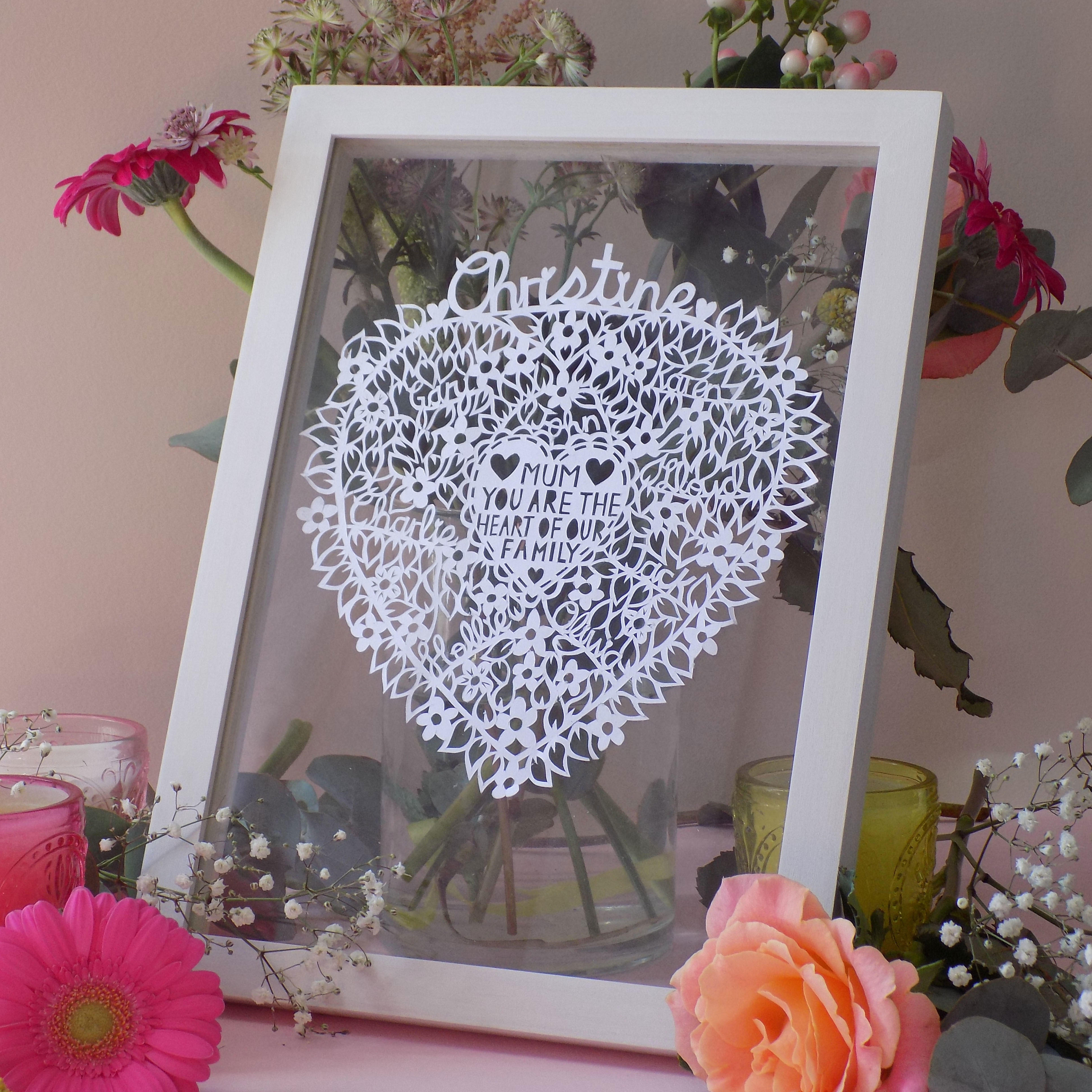A hand drawn hand cut paper cut love heart filled with flowers and the names of all the family, personalised for mums.
