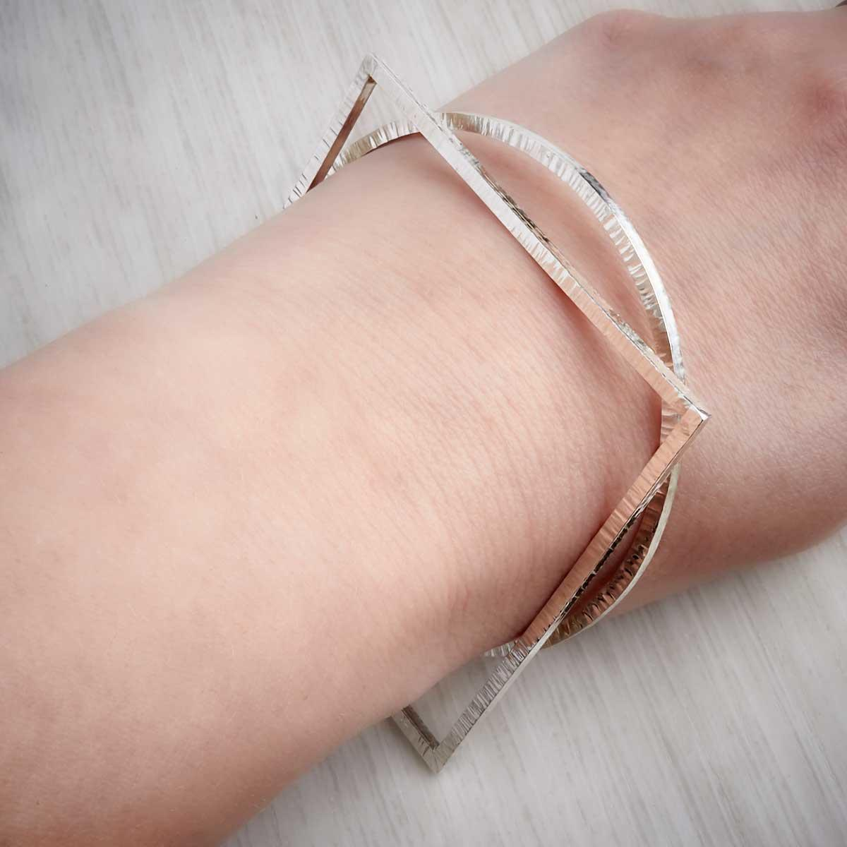 Contemporary handmade silver bangle stack by Emma White. Image property of THE JEWELLERY MAKERS.