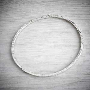 Hammered silver oval bangle, made by Emma White of THE JEWELLERY MAKERS.