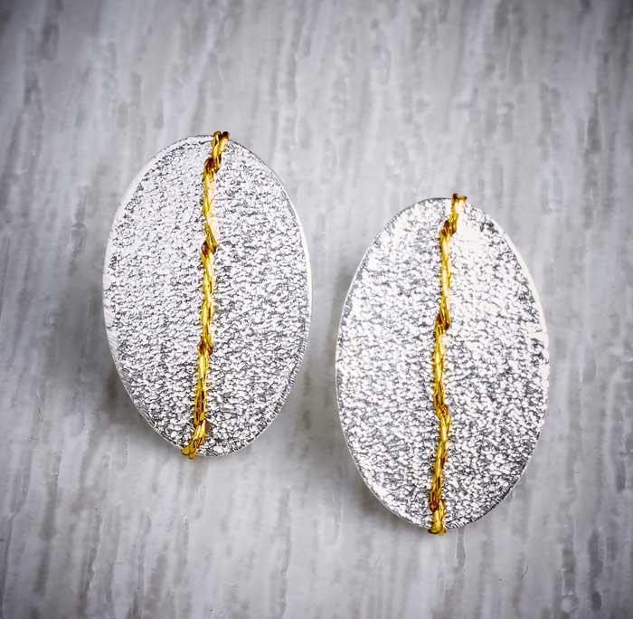 Silver sewn up textured stud earring with gold thread by Sara Buk