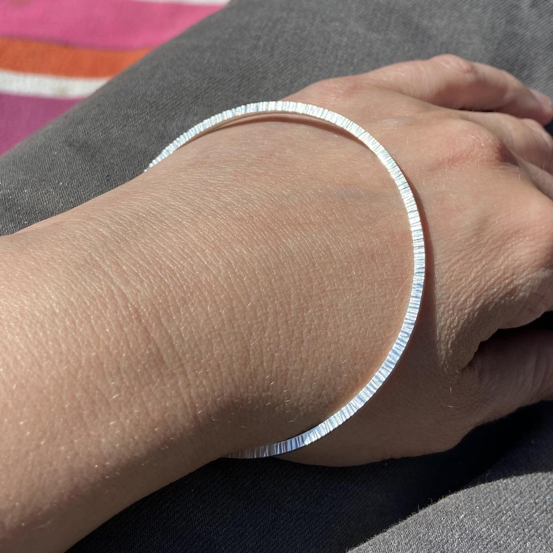 Hammered edge silver geometric round handmade bangle, worn on