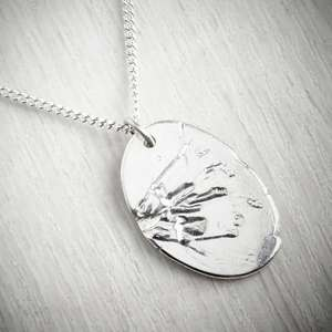 Handmade necklace with a daffodil imprint on a grey background. Made by Becca Macdonald, image property of THE JEWELLERY MAKERS.