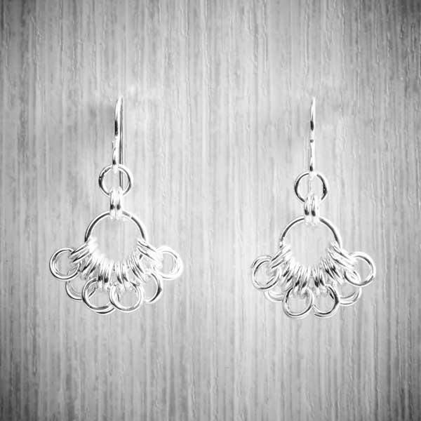silver Chainmaille earrings in a fan shape on a grey background