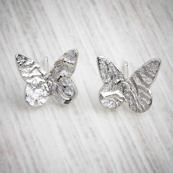 Handmade silver butterfly earrings, with reticulated surface on grey background