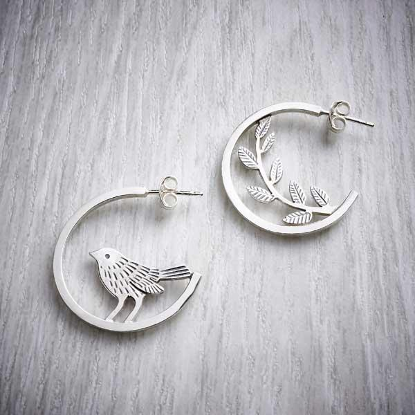 Mismatched silver hoops, with a bird and leaves by Helen Shere