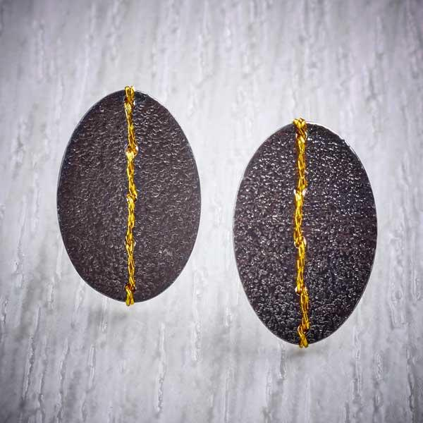 Oxidised (Blackened) Silver, Oval studs, sewn with Gold thread by Sara Bukumunhe. Image property of THE JEWELLERY MAKERS.