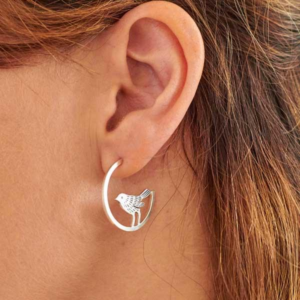 Mismatched silver hoops, with a bird and leaves by Helen Shere, worn on, bird