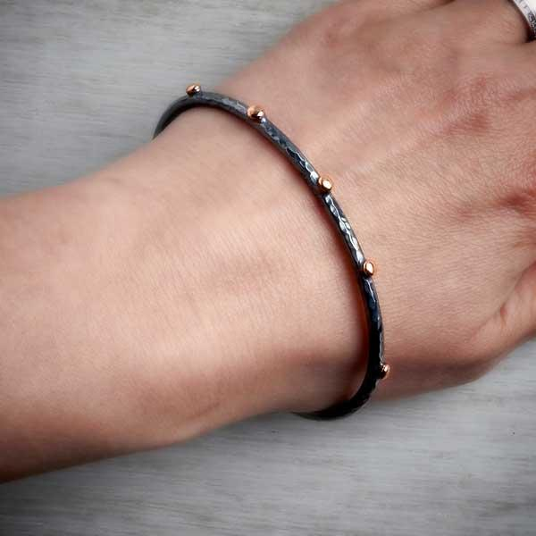 Handmade black silver bangle with rose gold nuggets on wrist