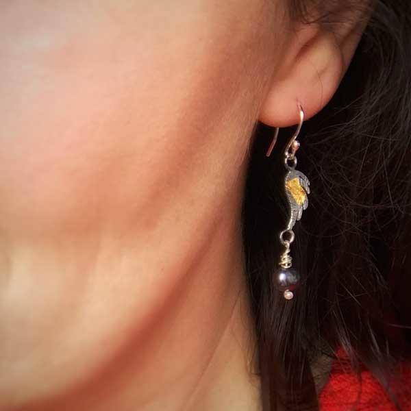 Silver, gold and Pearl Angel Wing Earrings, by Fi Mehra, worn on by woman with brown hair